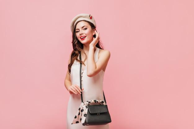 Mulher de vestido de seda e boina branca posa com bolsa crossbody no fundo rosa.