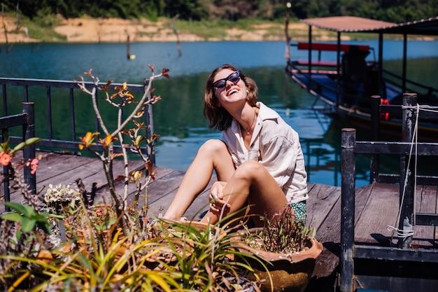 Mulher de vestido de verão e viagem de turista de jaqueta na tailândia, o parque nacional khao sok, uma vista incrível sobre barcos e lago.
