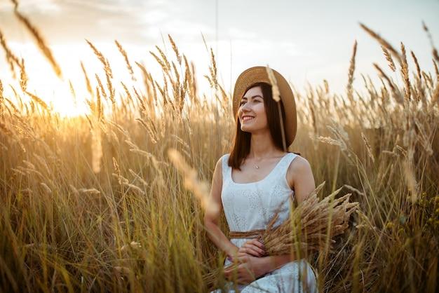 Mulher de vestido e chapéu de palha segurando buquê de trigo