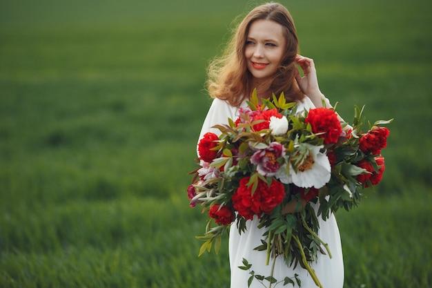 Mulher de vestido elegante em pé em um campo de verão