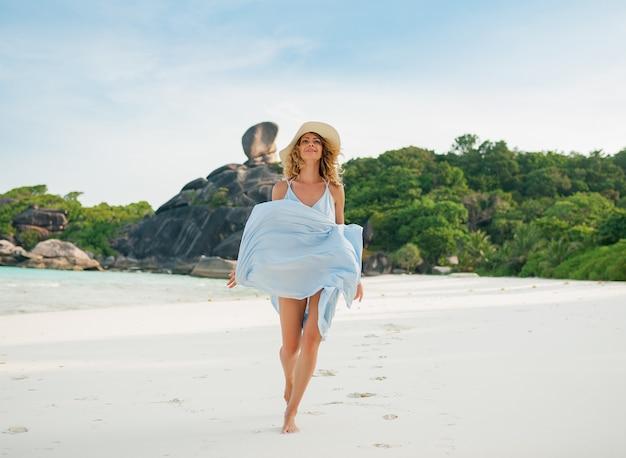 Mulher de vestido elegante, posando na praia em uma ilha paradisíaca tropical