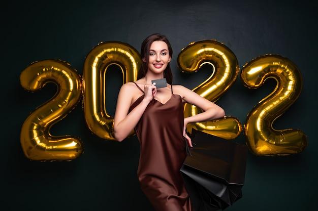 Mulher de vestido elegante segurar cartão de crédito e sacolas de compras em números de fundo preto ...
