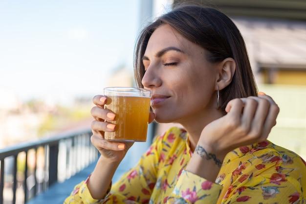Mulher de vestido em um café de verão apreciando um copo de kombuchá legal cheirando o cheiro com os olhos fechados