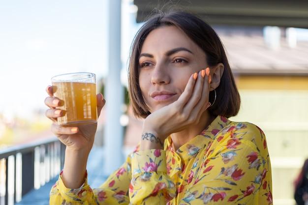 Mulher de vestido em um café de verão tomando um copo de cerveja legal de kombuchá