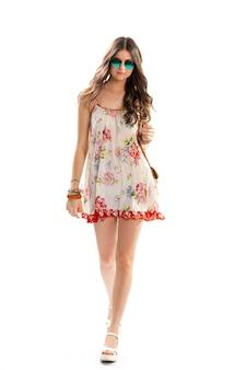 Mulher de vestido está caminhando. vestido floral curto e óculos escuros. colar pequeno com pendente. jovem modelo usa roupa de verão.