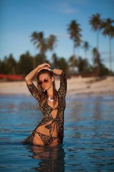 Mulher de vestido estampado de leopardo e maiô na praia tropical