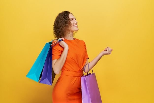 Mulher de vestido laranja segurando sacolas de papel, sorrindo.