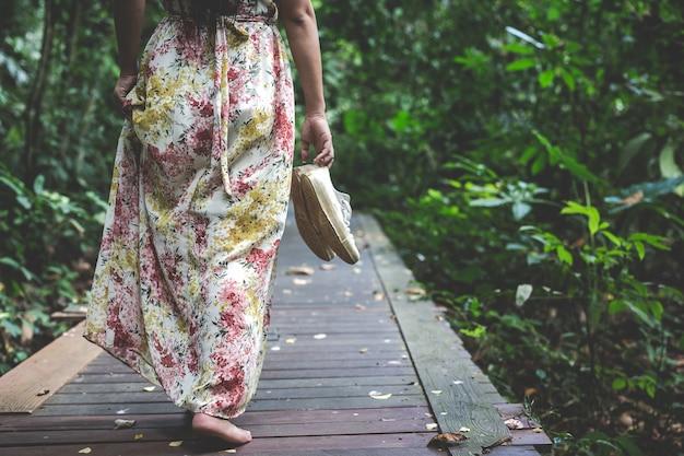 Mulher de vestido longo carrega seus sapatos andando no parque