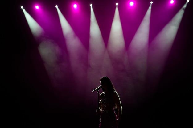 Mulher de vestido longo, realizando no palco. mulher cantando no palco em frente às luzes.