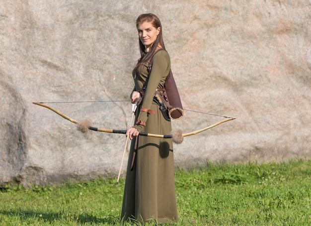 Mulher de vestido longo segurando um arco e flecha