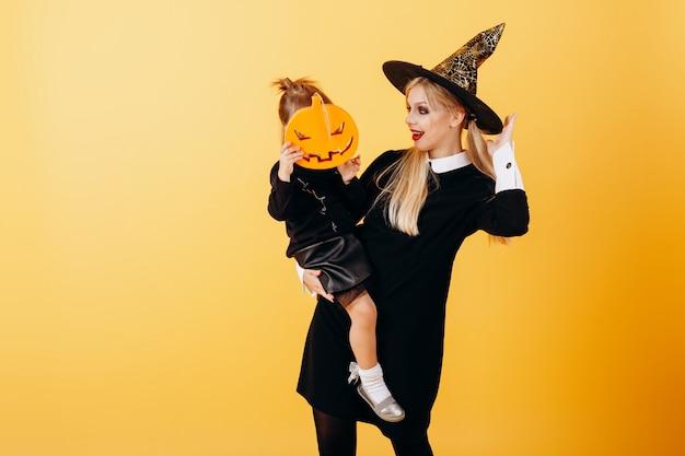 Mulher de vestido mascarada e chapéu posando contra amarelo segurando menina