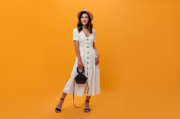 Mulher de vestido midi e chapéu de palha posando com bolsa em fundo laranja
