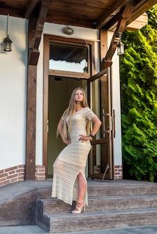 Mulher de vestido posando em pé na escada