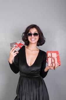 Mulher de vestido preto com caixas de presente