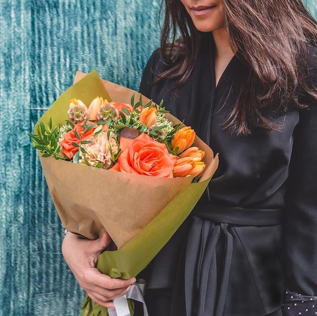 Mulher de vestido preto com um bouquet misto de papel.