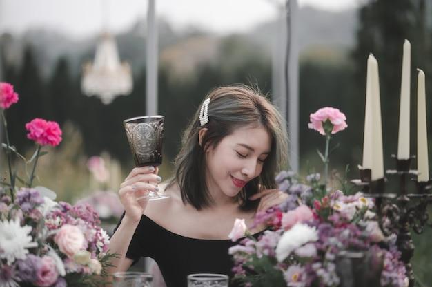 Mulher de vestido preto, desfrutando de um jantar romântico no jardim de flores, decoração vintage.