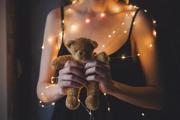 Mulher de vestido preto e luzes segurando o ursinho de pelúcia brinquedo