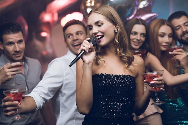 Mulher de vestido preto está cantando músicas com seus amigos.