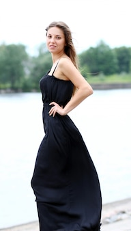 Mulher de vestido preto junto ao rio