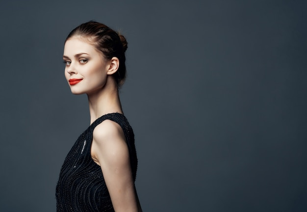 Mulher de vestido preto, lábios vermelhos, posando de paixão de luxo, aparência atraente