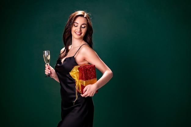 Mulher de vestido preto segurando caixa vermelha de presente e taça de champanhe.