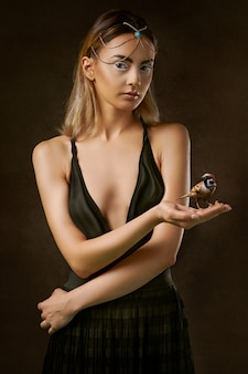 Mulher de vestido preto, segurando o pássaro marrom