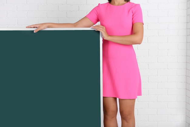Mulher de vestido rosa com lousa verde contra a parede de tijolos, close-up