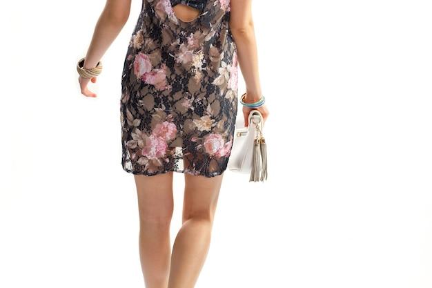 Mulher de vestido segura a bolsa. vestido floral escuro e bolsa. pulseiras de plástico coloridas. vista traseira do vestido de noite.