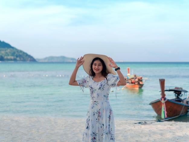 Mulher de vestido segurando chapéu de aba larga na cabeça em pé na vista do mar areia praia azul mar e céu