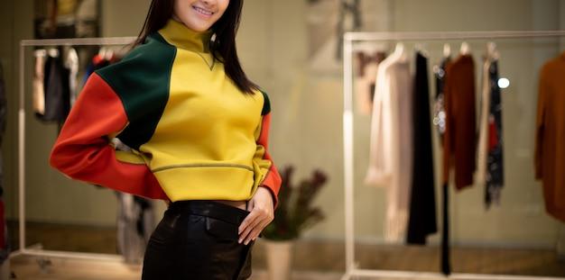 Mulher de vestido selecione nova coleção na prateleira