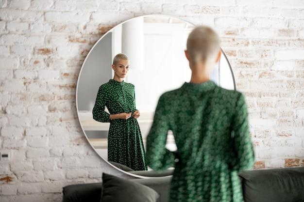 Mulher de vestido verde se olha no espelho em casa