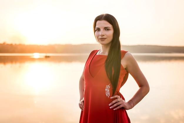 Mulher de vestido vermelho contra o pôr do sol no lago