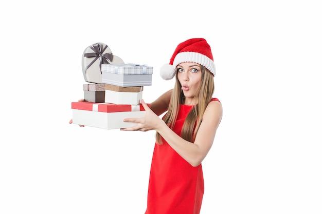 Mulher de vestido vermelho e chapéu de papai noel segurando caixas de presente