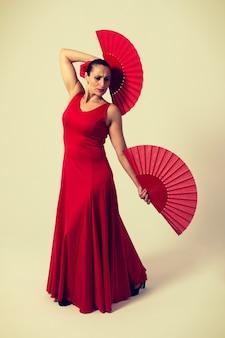 Mulher de vestido vermelho e fã dançando flamenco