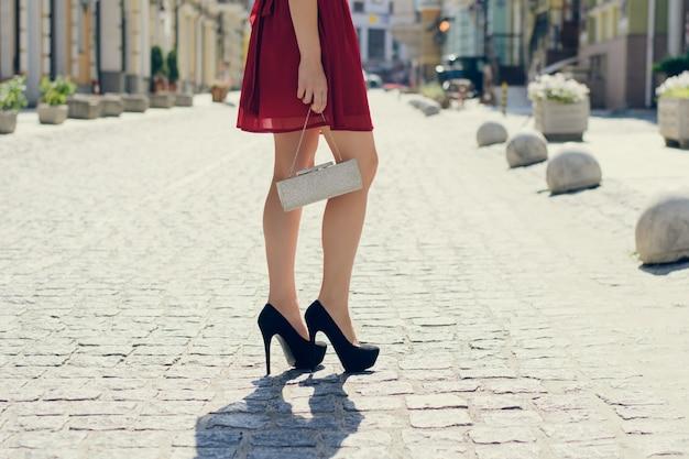 Mulher de vestido vermelho e rodas altas segurando a embreagem