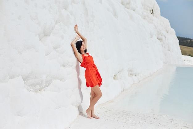 Mulher de vestido vermelho em travertinos brancos, pamukkale