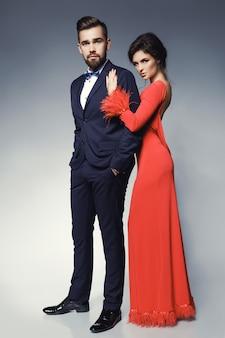Mulher de vestido vermelho lindo e homem vestindo terno clássico azul com gravata borboleta.