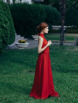 Mulher de vestido vermelho luxo princesa mascarada encanto de folhas verdes.