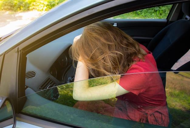 Mulher de vestido vermelho segurando a cabeça no volante