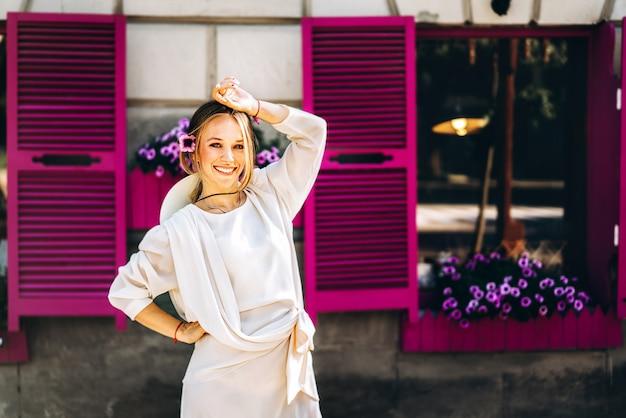 Mulher de vestido vintage branco na rua com janelas roxas por trás