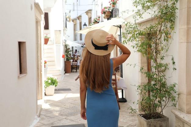 Mulher de viagem com chapéu de palha e vestido azul aproveitando as férias na itália