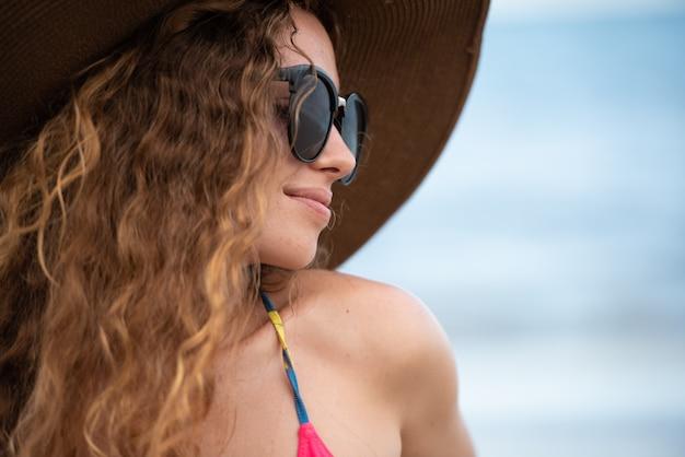 Mulher de viagem na praia com cabelo louro, chapéu e óculos de sol.