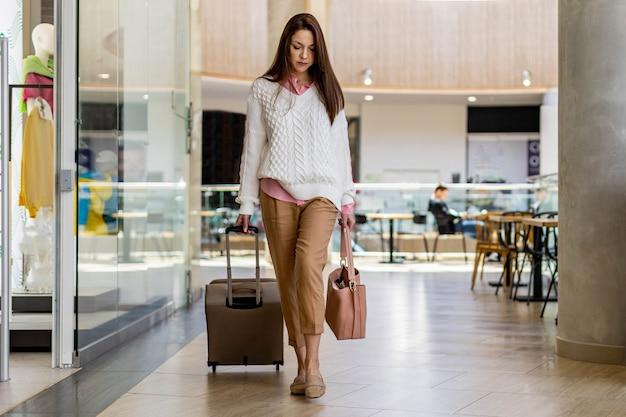 Mulher de viagens cansada com mala indo a lojas duty free aproveitando as compras no aeroporto internacional