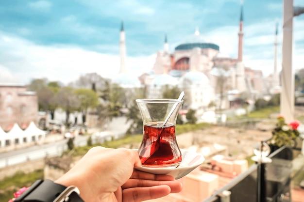 Mulher de viagens com chá turco, olhando a vista da hagia sophia em istambul, turquia