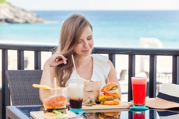 Mulher de viagens com hambúrgueres de fastfood, café e sucos em um café ao ar livre
