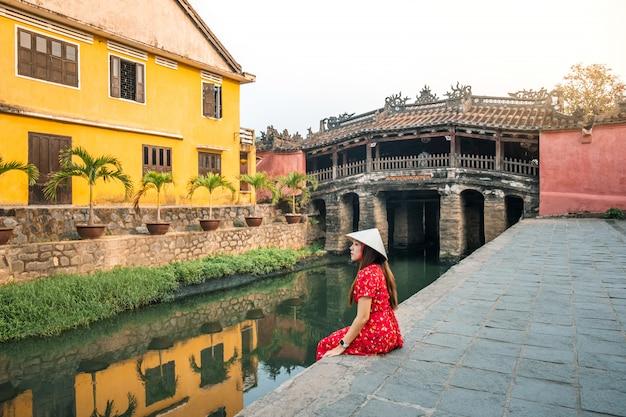 Mulher de viagens com ponte coberta japonesa, em hoi an, vietnã