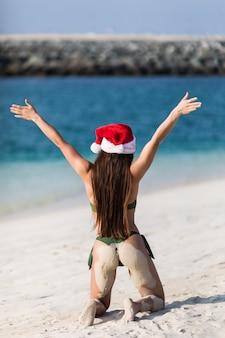 Mulher de viagens de férias de praia natal usando chapéu de papai noel e biquíni aproveitando o natal na praia tropical. vista traseira.