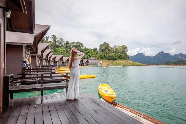 Mulher de viagens em pé no cais de uma casa de madeira em um lago com montanhas tropicais