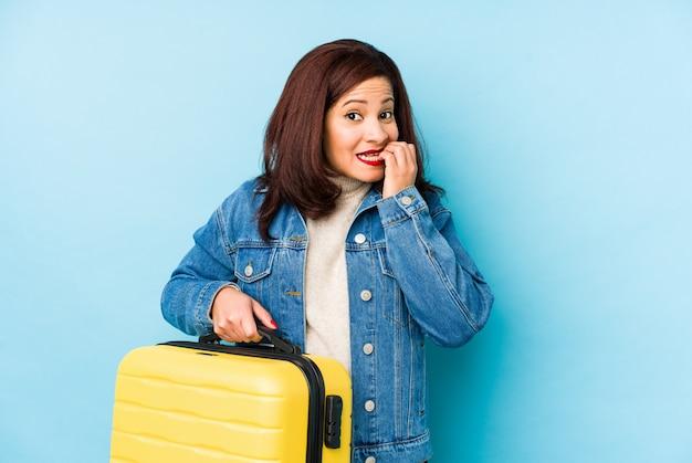 Mulher de viajante latino idade middlr segurando uma mala de roer unhas, nervoso e muito ansioso.