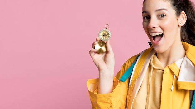 Mulher de viajante sorridente usando uma bússola com espaço de cópia